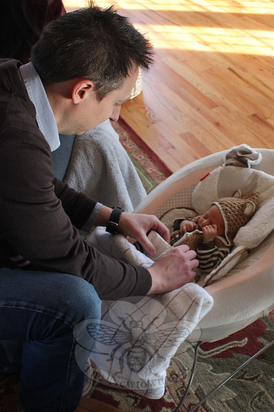Paul Wildgust kneels down to pick up his son Henry on January 7, four days after the newborn and his mother arrived home after the baby's birth. (Hicks photo)