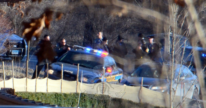 A pair of Newtown Police officers stand behind a Newtown cruiser at 4:38 pm, guns drawn, facing the vehicle of a suspect who held local and state police in a standoff situation for nearly two hours Wednesday afternoon. The police officers and their cruiser and the suspect vehicle were on Oakview Road; Wasserman Way is behind them. (Voket photo)