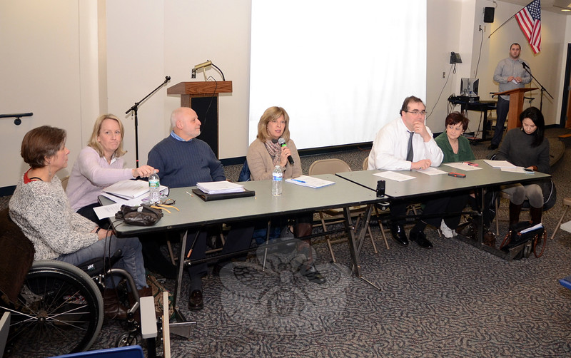 Members of the Sandy Hook Permanent Memorial Commission attending a January 20 public input session at Newtown High School included, from left, Sarah Middeleer, Tricia Pinto, Vice Chair Alan Martin, Donna Van Waalwijk, Daniel Krauss, Joanne Brunetti, and Agni Pavlidou-Kyprianou. Chairman Kyle Lyddy is pictured far right at the podium. The session drew the attention of several television crews but fewer than a dozen residents turned out. (Voket photo)