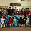 """Fraser Woods Montessori School head of humanities and Dean of the Middle School Wendy Musk, sixth from the right in the back row, stood with her middle school students around her """"Global Game"""" board on Wednesday, January 14. (Hallabeck photo)"""