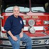 """Sandy Hook Volunteer Fire & Rescue Company Chief Bill Halstead at Sandy Hook's main fire station on Riverside Road in front of the company's fire vehicle known as """"Ladder 440"""" or the """"Quint"""" truck. Chief Halstead this week observed 50 years as a Sandy Hook firefighter. (Gorosko photo)"""