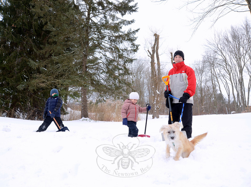 John Masotta and his children Noah, 8, left, and Ivy, almost 5, walk through the snow Tuesday with their dog Lainey. The Grand Place residents soon stepped across the street to help a neighbor clear snow. (Bobowick photo)