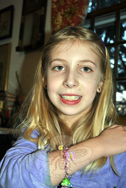 Nine-year-old Lauren Milgram of Sandy Hook shows off the butterfly charm she designed. She is one of 12 winners in the 2014 Charm It! Crayola Creativity Design-A- Charm Contest.	(Crevier photo)