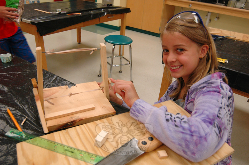 Camper Lizzy Gotschlich worked on building a catapult on Tuesday, July 7, during Newtown Con-tinuing Education's Design It, Build It, Launch It camp's second day of the first of two, two-week long sessions. (Hallabeck photo)