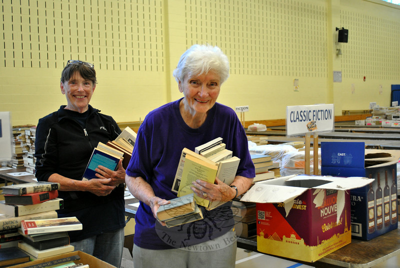 """Janet Woycik, left, and Carm O'Neil, both retired librarians and volunteers with Friends of the C.H. Booth Library, have their arms full as they set up the Classics Fiction section of the Annual Book Sale, Monday morning, July 7. Volunteers were busy in the cafetorium and gymnasium of Reed Intermediate School, setting up for the third-largest book sale in New England. Set up began July 1, in preparation for opening day, Saturday, July 12, at 9 am. For details, visit  <a href=""""http://www.chboothlibrary.org"""">http://www.chboothlibrary.org</a>. (Crevier photo)"""