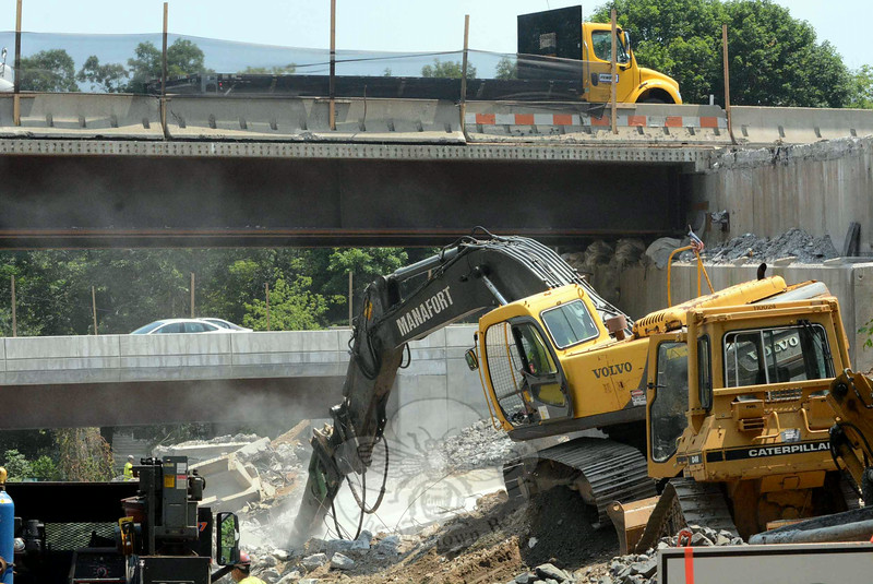 In this photo taken midday on Monday, July 7, on Center Street in the Riverside section of Sandy Hook, masonry dust is flying as an excavator, lower right corner, is used for demolition work as part of the state project to replace the two Interstate 84 bridges that cross above Center Street. At the top of the photo, a steel truck is seen traveling westward on I-84. At center left, cars are seen moving eastward on I-84. The construction site lies just west of I-84's Rochambeau Bridge, which crosses the Lake Zoar section of the Housatonic River. (Gorosko photo)