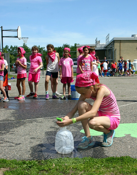 Skyler Howard concentrates during the Sponge Race. Children had to wet a sponge from a bucket of water on one side of their section of playground, then run about ten yards and squeeze the water into a gallon jug, all while racing teams of other children doing the same thing. The object was to be the first team to fill the jug with water. (Hicks photo)