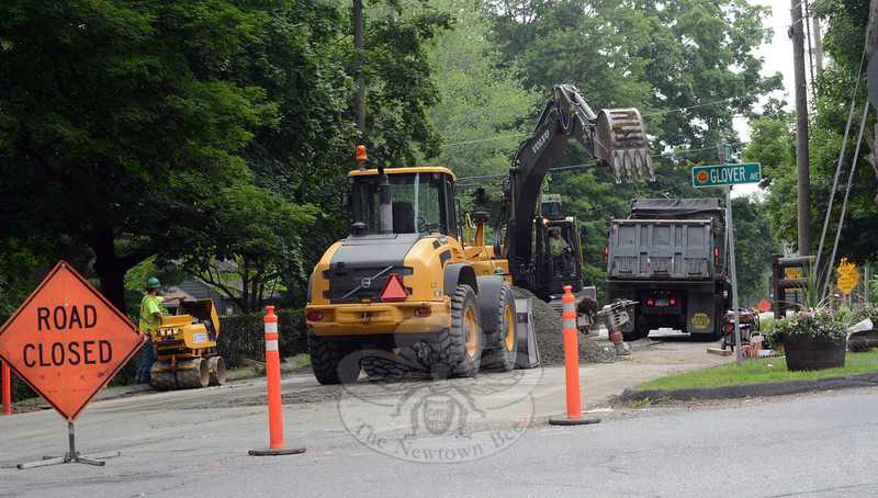 In this July 15 view, which looks southward on Queen Street from its intersection with Glover Ave-nue, workers for Aquarion Water Company are seen using a roller, loader, excavator, and dump truck for a water pipe replacement project. In the coming weeks, the workers will be replacing sections of outdated pipe on Queen Street. During the construction, certain sections of Queen Street lying between its intersections with Glover Avenue and Mile Hill Road will be closed to through-traffic with detours provided for motorists. (Gorosko photo)