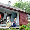 "Docents ""Mistress"" Patty Graves, left, and Melissa Houston sit on the back steps outside the kitchen door. Above them is a large stone chimney that vents smoke from a central kitchen fireplace, which was lit and used for cooking Wednesday. (Bobowick photo)"