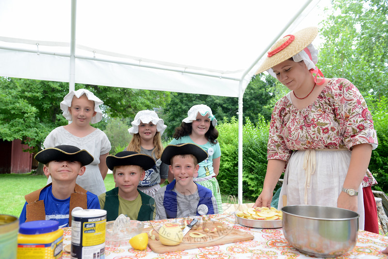 Working with a group of campers was docent Mairin Hayes as she and the students prepared a recipe for apple crisp. From left, the young ladies are Anna Metzker, Emma Hannah, and Grace Zatulskis; the young men are Ryan Ward, Conrad Chapman, and Connor Troy. (Bobowick photo)