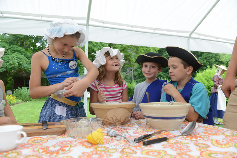 The annual History Camp at the Matthew Curtiss House on Main Street, sponsored by the Newtown Historical Society, made colonial times look downright appetizing to campers on July 15. Jocelyn Ba-zuro greased an aluminum baking dish, while Julia Wologodzew stirred a large bowl of fruit. Nathaniel Lewis, center, and Jeffrey Hanna, right, cut and squeeze lemons for their juice, and other ingredients for the blueberry pudding cake they were making. (Bobowick photo)