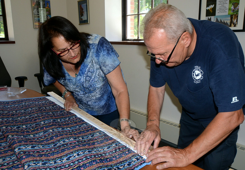 Local artist and quilter Stefanie Lagana teaches town worker Peter D'Accolti how to carefully Velcro framing strips along the edges of memorial quilts for proper hanging and preservation recently at the Newtown Municipal Center. (Voket photo)