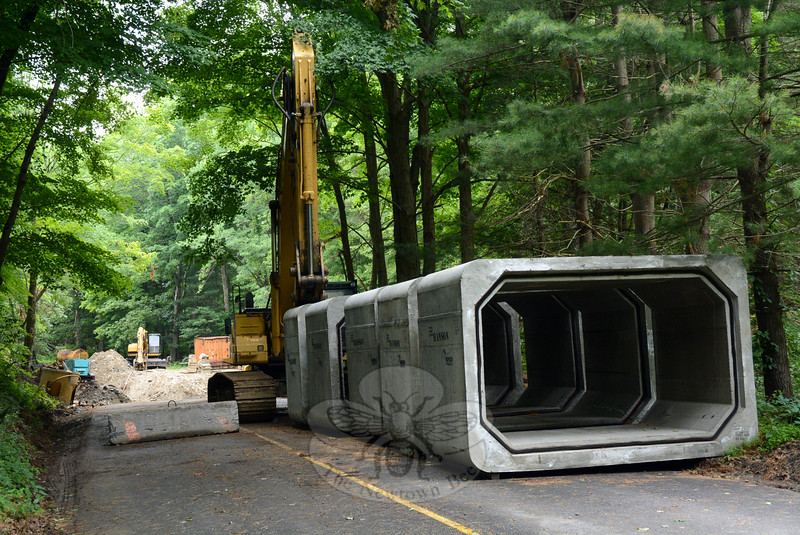 Midday on Monday, July 14, a line of five reinforced-concrete segments of a box culvert sat on Poverty Hollow Road adjacent to the construction site for a new bridge crossing at the Aspetuck River, near the parking lot entrance for Centennial Watershed State Forest. The concrete structures shown are about eight feet tall. (Gorosko photo)