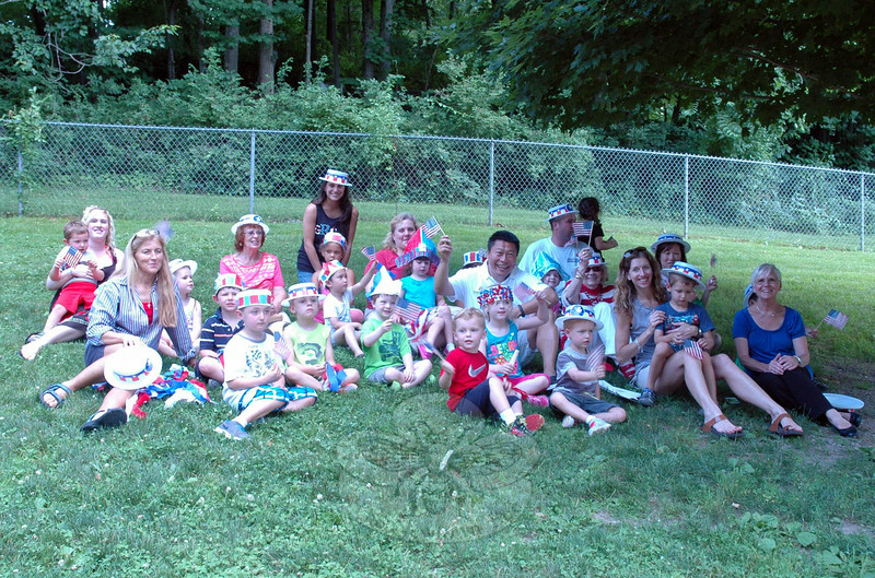"A gathering at the Children's Adventure Center celebrated the Fourth of July ahead of schedule on July 1. Eventgoers wore red, white, and blue hats, and waved small American flags to honor the then-upcoming holiday. State senate hopeful Tony Hwang, seated center right, was one of the many guests for the ""Salute to July 4"" event. (Hallabeck photo)"