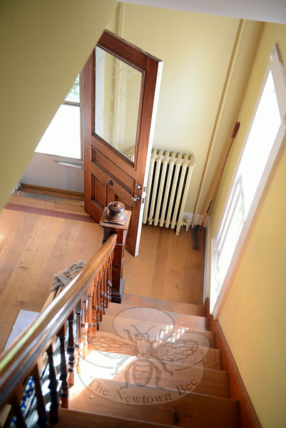 A view from the front staircase looks down on the entryway, which is bright with natural light coming in a side window. The solid wooden front door also contains a frosted glass window that offers a view of a brief front walkway leading to Main Street. (Bobowick photo)