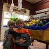 Co-owner Sue Shortt (in background), 5-year-old Jesse and older brother James, 6, hold Blackie the chicken inside their parents' market at Shortt's Farm Center at 52 Riverside Road in Sandy Hook. The market sells locally grown, and primarily organic, produce, and carries a wide variety of goods from area farms, including ice cream from Ferris Acres Creamery in Newtown. Other products offered include jams, maple syrup, soaps, and dairy.  (Bobowick photo)