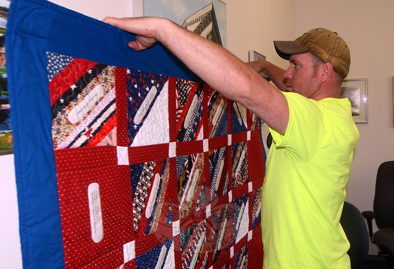 Town worker Kevin Belden tests the newly installed framing and suspension hardware on one of the many memorial quilts that arrived in town from across the country in the wake of 12/14, and are displayed throughout the Newtown Municipal Center. (Voket photo)