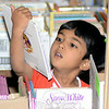 Four-year-old Arya Thirumurthi seemed lost in a world of fantastical choices with a seemingly limitless number of Disney picture books laid out before him last Saturday morning at the annual CH Booth Book Sale at Reed Intermediate School. The renown book sale drew book lovers and collectors from far and wide over the course of several days. (Voket photo)