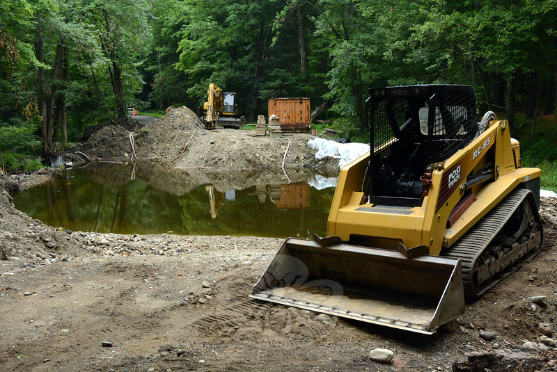 Earthmoving equipment is parked on both sides of a pool of water where three parallel box culverts will be installed to serve as the foundation for a new Poverty Hollow Road Bridge across the Aspetuck River. The bridge project is scheduled to be done by August 15.