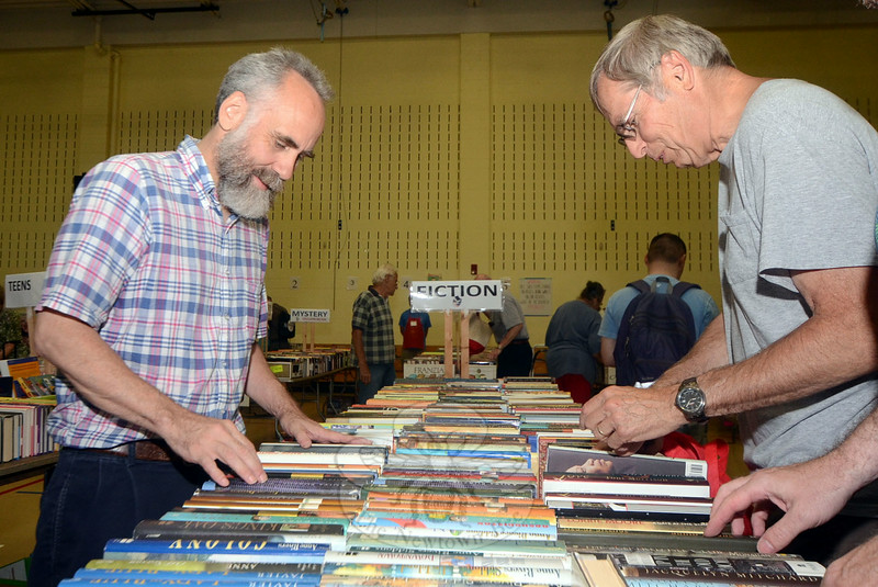 Dana Trodella, who came to the book sale Saturday morning from Boston, bumped into Drew Griffin, who made the drive in from Cambridge, over the fiction selections. (Voket photo)