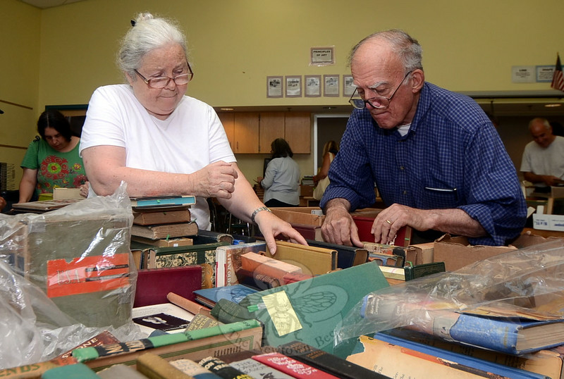 Holly Beckett of Canton and Frank Volkman of Cold Spring, N.Y., both devoted much of the first few hours of the book sale to examining the rare book offerings at Reed School July 12. (Voket photo)