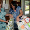 Sandy Hook artist Stefanie Lagana and Newtown Human Resources Director Carole Ross examine one of several memorial quilts sent to Newtown in the wake of the Sandy Hook tragedy. Ms Lagana, an expert quilter, volunteered to assist the town in preserving the special quilts and properly framing them for permanent display. (Voket photo)