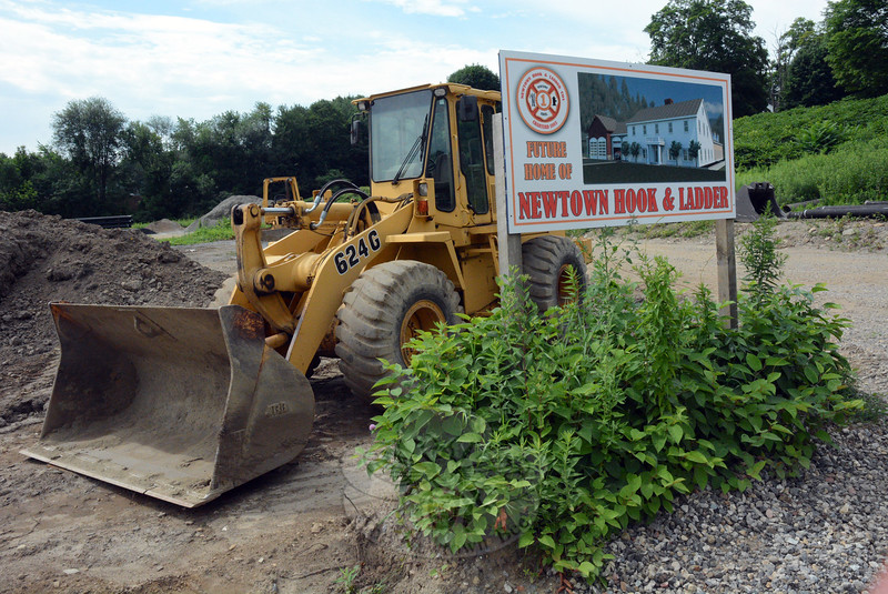 At 12 Church Hill Road, a loader is parked behind a sign showing an architect's rendering of the Newtown Hook & Ladder firehouse planned for the site. (Gorosko photo)
