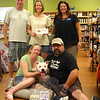 """Bronco, a 4-year-old pitbull, was joined by owners Trina and Chris Cain in one of the comfortable dog beds at Your Healthy Pet on July 21. That morning, the Cains were met by Town Clerk Debbie Aurelia Halstead, standing at right, who formally presented Bronco and his """"parents"""" with the Newtown #1 dog tag, an honor presented to one lucky dog each year after the June 30 deadline to obtain or renew dog licenses by town residents. The group gathered at the new location of Your Healthy Pet, at 61 Church Hill Road. There they were greeted by Tom and Mary-Kay Novak, standing left and center, who co-own the business with their son Ryan. The Novaks presented the Cains with a $50 Your Healthy Pet gift certificate. (Hicks photo)"""