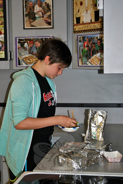 Meredith Taylor, 12, adds salsa to her chicken recipe during the Tuesday class focused on Spanish cuisine. (Crevier photo)
