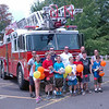 Standing in the back row from left are Newtown Hook & Ladder Company #1 firefighters Ray Corbo, Jason Rivera, and Jason Shuttleworth with with Design It, Build It, Launch It instructor Rick Lowry and intern Rachel DiVanno. Campers pictured on Wednesday, July 15, from left, are Lizzy Gotschlich, Jesse Kinsmann, Jack Dyson, Connor Adams, Dante Verna, Jett Lyons, and Thomas Simms. (Halla-beck photo)