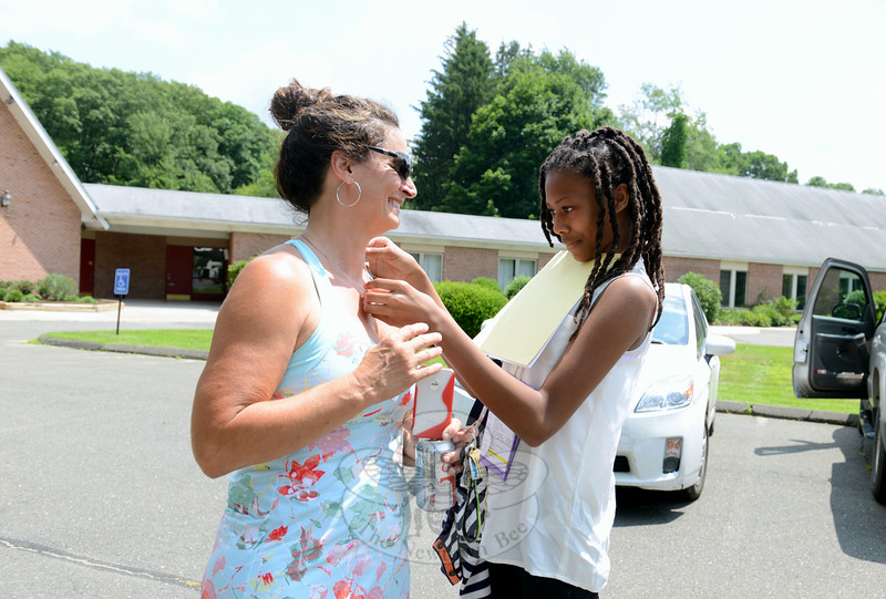 Resident Mary Sireci greets her summer guest Aza Smith, who has visited with her in the past. Aza admires Ms Sireci's necklace. (Bobowick photo)