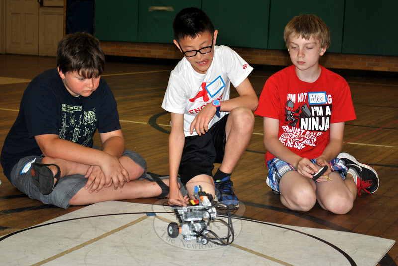 Oscar Roberts, left, and Alec Almeter, right, watch as Henry Villodas launches his robot into the circle. (Crevier photo)