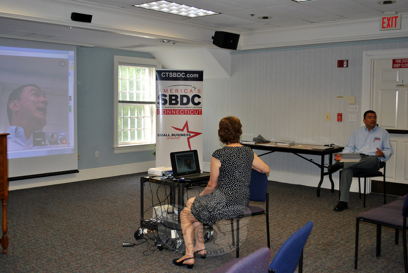 Andy Forsyth, reference librarian, at computer, and Nelson Merchan of the Connecticut Small Business Development Center, demonstrate the Virtual SBDC Center at the C.H. Booth Library, during a June 23 introductory program. (Crevier photo)