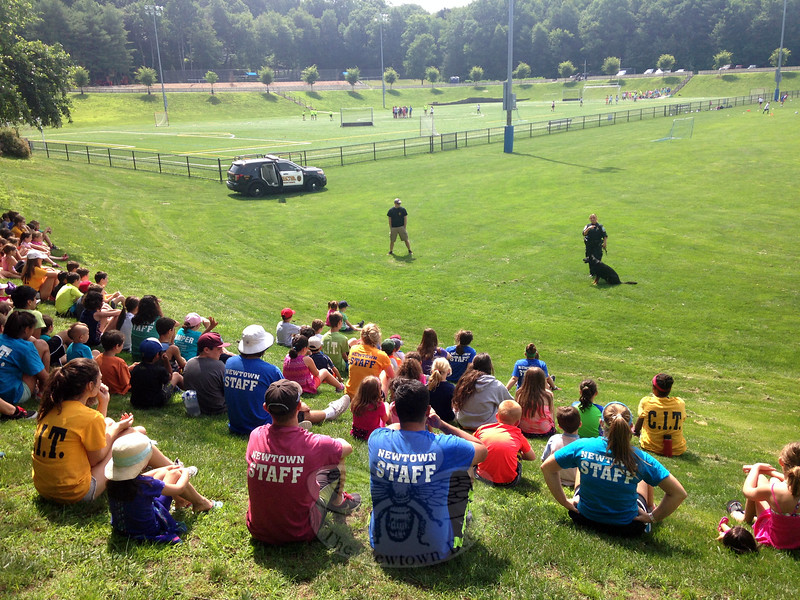 Newtown Police Department Patrol Officer Felicia Figol, who is the police department's dog handler, far right, led St Michael, the department's German Shepard, through a demonstration for campers at Treadwell Park on Friday, June 19. (Gallagher photo)