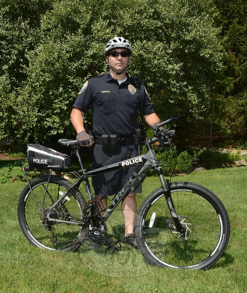 Police Patrol Officer Leonard Penna is again traveling on local roads on a bicycle. The po-lice bicycle patrol is part of the community policing program. For the next three months, Officer Penna will be on bicycle patrol in the town center, at Fairfield Hills, and at Dickinson Park, among other areas. The mountain bike is equipped with specialized tires suited for varied terrain, including roadways and wooded areas.  (Bee Photo, Gorosko)