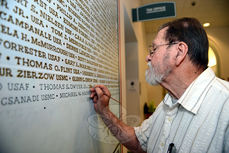 Southbury artist David Merrill adds new names to a mural listing Newtown's servicemen and women. Since his artwork was unveiled late last year, he has received additional names, some of which he painted in Tuesday morning at the Newtown Municipal Center. (Bobowick photo)