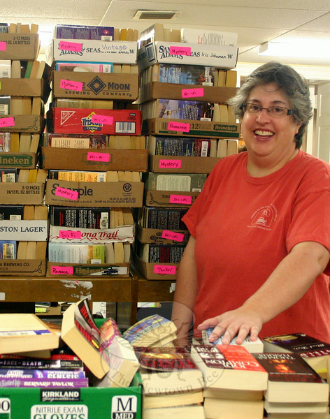 Kelley Johnson stands within a small selection of the growing collection of science fiction and mystery books that will be part of the Friends of Booth Library Annual Book Sale offering July 12–16. (Hicks photo)