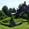 A tightly symmetrical garden comprised of topiary and flowering plants stands in the northern side yard of the 1785 Kenyon residence at 62 Main Street. (Gorosko photo)