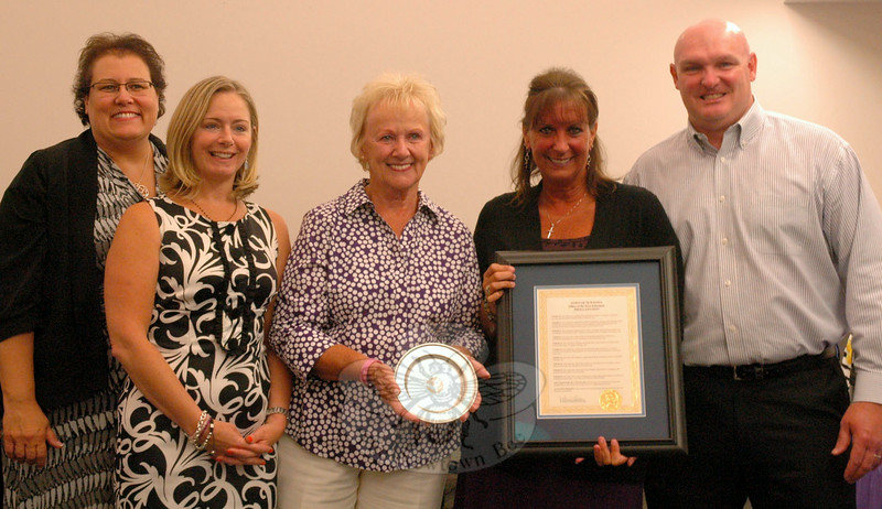 GE Capital's Joni Capoccitti, second from right, was presented with a proclamation and a pewter bowl with the Newtown town seal from First Selectman Pat Llodra, third from left, at the Board of Education's Monday, June 30, meeting. Standing with the pair, from left are GE's Anne Alzapiedi, Elizabeth Rollo, and Tom Kelleher. (Hallabeck photo)