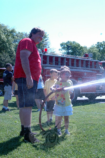 Hawley Elementary School held its Field Day on Friday, May 29. For the event, Newtown Hook & Ladder Co. #1 had trucks on display. Hood & Ladder's Sean Reilly showed students like Stella Wasley the hose on one truck to spray water. (Hallabeck photo)