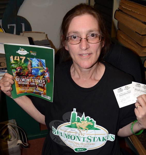 Bridget Seaman displays the T-shirt, program, and a pair of betting vouchers she brought home from the Belmont Stakes June 6, where for the second time in her life, she witnessed a horse racing Triple Crown victory. (Voket)