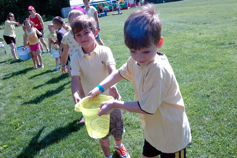 Hawley student Andrew Smiley, right, was handed a bucket filled with water Pedro Padilla at the Bucket Brigade station at Hawley's Field Day. (Hallabeck photo)