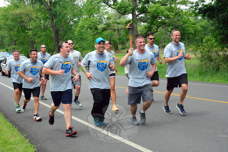 On June 5, Newtown Police Department officers and Garner Correctional Institution staff members participated in the Newtown leg of the 2015 Law Enforcement Torch Run event in support of the Special Olympics of Connecticut Summer Games. The runners followed a 5.1-mile course from the Dodgingtown Firehouse to Exit 10 of Interstate 84. They are shown running on Sugar Street, near Castle Hill Farm. Newtown Police Officer Bart Lorancaitis is carrying the Special Olympics torch. Others shown running include Newtown police officers Michael Caramadre, William Chapman, John McDermott, Steven Borges, Matthew Wood, and Daniel McAnaspie. (Gorosko photo)