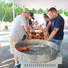 Michael Heneghan, left, works at cracking freshly boiled lobsters across from Quinn Fontaine, among other fire company volunteers at work at the weekend's 28th annual LobsterFest at the Sandy Hook Volunteer Fire & Rescue Co. firehouse. (Bobowick photo)