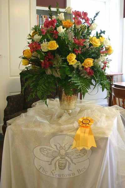 "Judges were impressed with Peggy Townsend's large floral arrangement for ""Joy! 50 Years of Celebrations,"" a standard flower show presented last week by the Town & Country Garden Club of Newtown. A gold speckled vase atop a table with a white tablecloth, over which Ms Townsend had placed some gold speckled overlay, held a beautiful arrangement of white and yellow roses, white stock, Alstromeria, bear grass fern, English privet and lemon leaves. The design, shown here, was awarded both a blue ribbon and a Judges Design Award. Notes by the judges of that class celebrated Ms Townsend's work, saying ""beautiful integration of plant material is a traditional mass design. Reflects the fullness of life!"" There are 20 design entries for visitors of Booth Library on June 12 and 13 to con-sider, four in each of five available divisions, displayed among the main and upper floor of the library. In the lower meeting room, guests found more than 100 horticulture entries, including a number that were given special awards. The special two-day display was a celebratory event for the club, which cele-brated its 50th anniversary in 2014. (Hicks photo)"