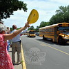 Newtown Middle School educators waved goodbye next to teachers and staff at his school, while holding smiley faces, as buses left the school for the last time this school year. (Hallabeck photo)