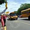 Newtown Middle School Principal Tom Einhorn, left, waved goodbye next to teachers and staff at his school, while holding smiley faces, as buses left the school for the last time this school year. (Hallabeck photo)