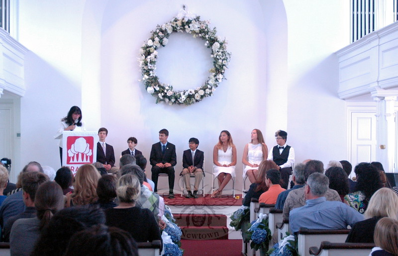Fraser Woods Montessori School eighth grade graduates looked on as humanities teacher and Dean of the Middle School Wendy Musk spoke. Students pictured from left are Gregory McKenna, Elliot Siegel, Aaron Squibb, Rishav Basu, Michaela Stowell, Bridget Gattinoni, and Jessie Meder. (Hallabeck photo)