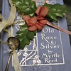 Library volunteers wonder about the back story of this book, one of several in a collection by author Myrtle Reed, that has a silk rose and silver mustard spoon tenderly attached with a satin ribbon. (Crevier photo)