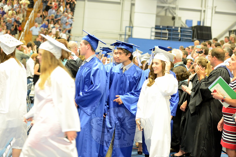 Students round the corner as they enter the auditorium and head down the center isle where they sit during graduation Tuesday. (Bobowick photo)